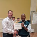 color photo of TJ Greenier accepting a certificate of appreciation from a grad student at UMD iSchool