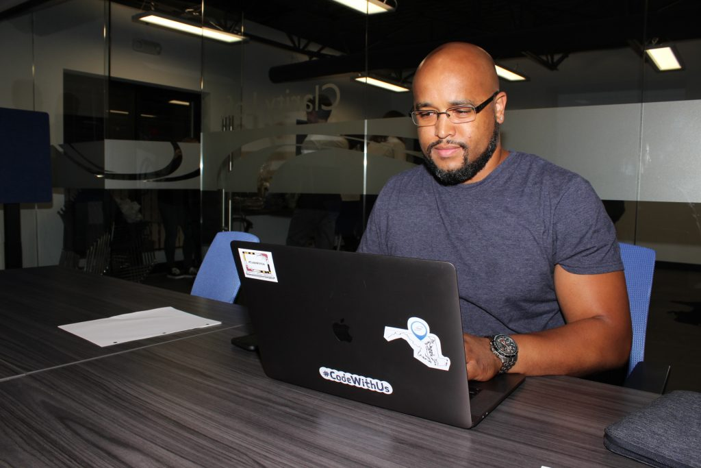 Chris Howard is teaching college courses. In this photo, he works on a laptop at Clarity's offices.